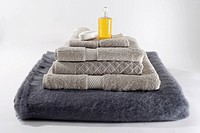 Stacks of folded towels with a bar of soap and massage oil on top