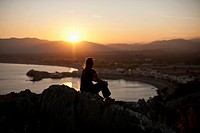 A silhouetted person sitting atop a hill watching the sunset, Rhodes, Greece
