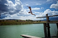A young boy jumping into a lake