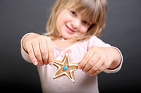 A girl holding out up a star shaped Christmas cookie