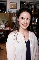 A woman standing in an antiques shop