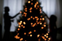 Silhouette of mother and daughter decorating a Christmas tree (thumbnail)