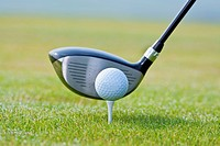 closeup of a golf ball and club on green grass _ club out of focus