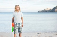 Spain, Mallorca, Boy with water gun on beach