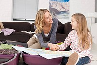 Germany, Leipzig, Mother and daughter looking at map, smiling (thumbnail)