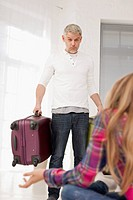 Germany, Leipzig, Father and daughter with packed luggage in apartment