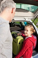 Germany, Leipzig, Father and daughter loading luggage into car