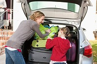 Germany, Leipzig, Mother and daughter loading luggage in car