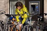 Germany, Bavaria, Munich, Mid adult woman locking bicycle (thumbnail)