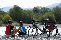 Germany, Bavaria, Man and woman sitting by bicycle (thumbnail)