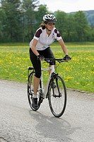 Germany, Bavaria, Mid adult woman riding bicycle (thumbnail)