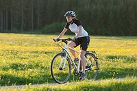 Germany, Bavaria, Mid adult woman riding bicycle