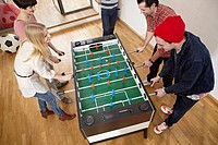 Germany, Cologne, Men and women playing table soccer (thumbnail)