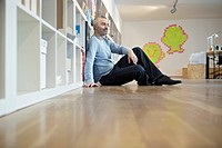 Germany, Cologne, Mature man sitting on floor