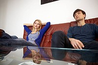 Germany, Cologne, Man and woman sitting on couch