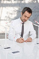 Germany, Leipzig, Businessman with wind power model on desk (thumbnail)