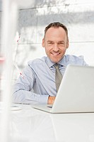 Germany, Leipzig, Businessman using laptop with wind power model