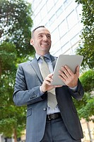 Germany, Leipzig, Businessman using digital tablet, smiling (thumbnail)