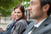 Germany, Leipzig, Business people sitting on bench, smiling
