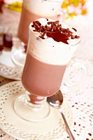 Two cups of hot chocolade with whipped cream. Delicious drink with nice decotation, standing on elegant plates.