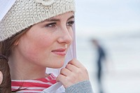 Close up portrait of pensive teenage girl in knit hat and hood