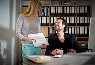 Germany, Cologne, Man and woman working in office, smiling
