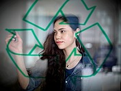 Germany, Cologne, Young woman drawing recycling symbol on glass
