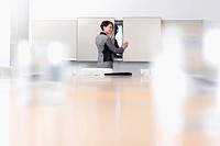 Businesswoman opening cabinet in conference room