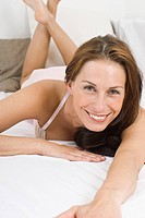 Germany, North Rhine Westphalia, Dusseldorf, Young woman lying on bed, smiling, portrait