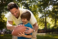 Caucasian father teaching son to play football