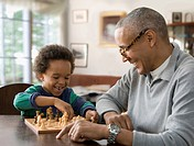 Grandfather and grandson playing chess together