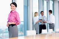 Portrait of smiling businesswoman standing at window in conference room with co_workers in background
