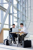 Businessman in wheelchair and co_worker using laptop at table in modern office