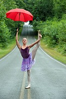 Caucasian ballerina dancing on remote road with umbrella
