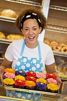 Black baker holding tray of cupcakes