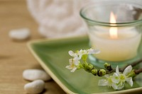 Delicate spring cherry blossoms, towel and candle in a zen spa atmosphere