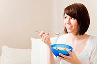 Young woman eating a bowl of muesli in her living room