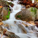 HDR image of a frothy mountain stream through boulders capture with a long exposure