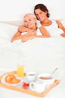 Couple lying on a bed with the breakfast served on a tray