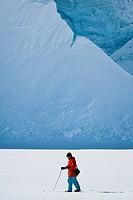Man moves on skis. Glacier in background. Antarctica