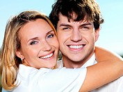 portrait of young happy beautiful couple on blue skiy background