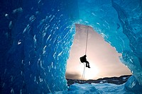 COMPOSITE: View from inside an ice cave of an iceberg frozen in Mendenhall Lake as an ice climber rappels down a rope, Juneau, Southeast Alaska, Winte...