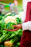Man _ only hands to be seen _ in supermarket as shop assistant, he is carrying a cauliflower
