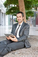 Germany, Leipzig, Businessman sitting at tree and using digital tablet