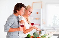 Young couple having a glass of red wine while cooking