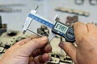 Taking a measurement with calipers, tool production