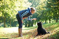 woman with black dog on a walk in the park
