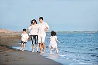 happy young family have fun on beach run and jump at sunset