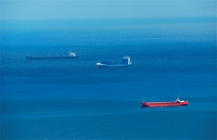 Three big cargo ships in deep blue sea