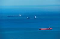 Three big cargo ships in deep blue sea